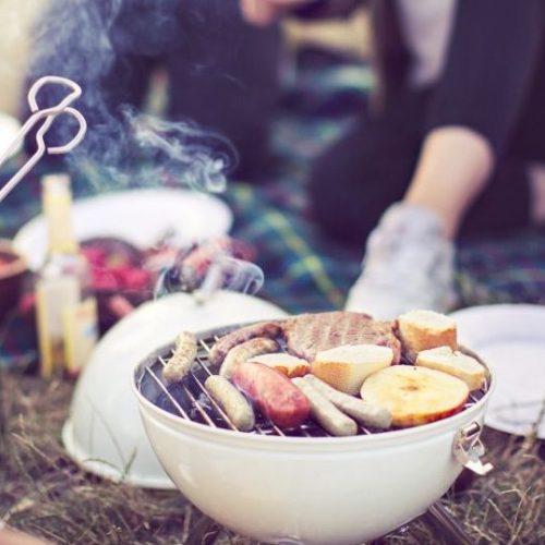 Junge Leute grillen Fleisch und Vegetarisches