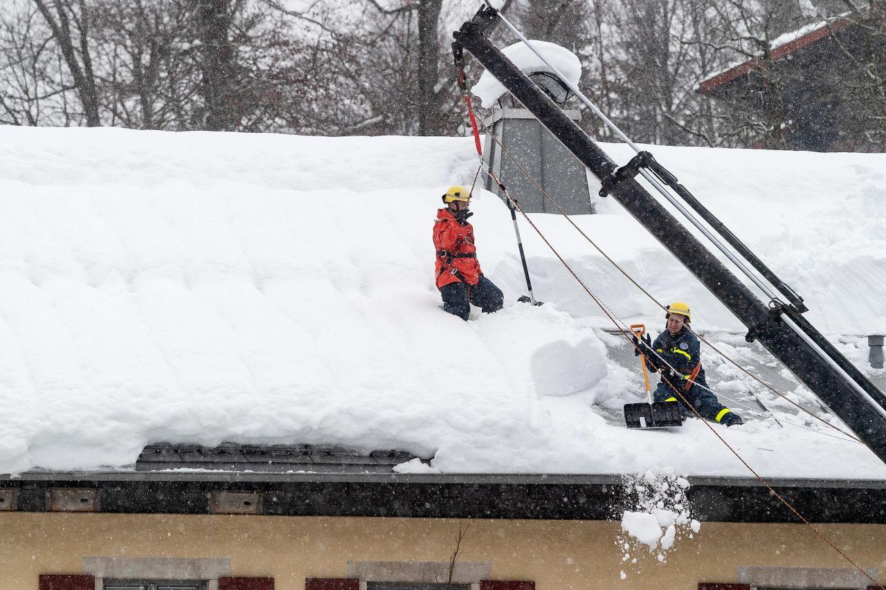 Zwei Helfer befreien ein Dach von einer gefährlichen Schneelast.