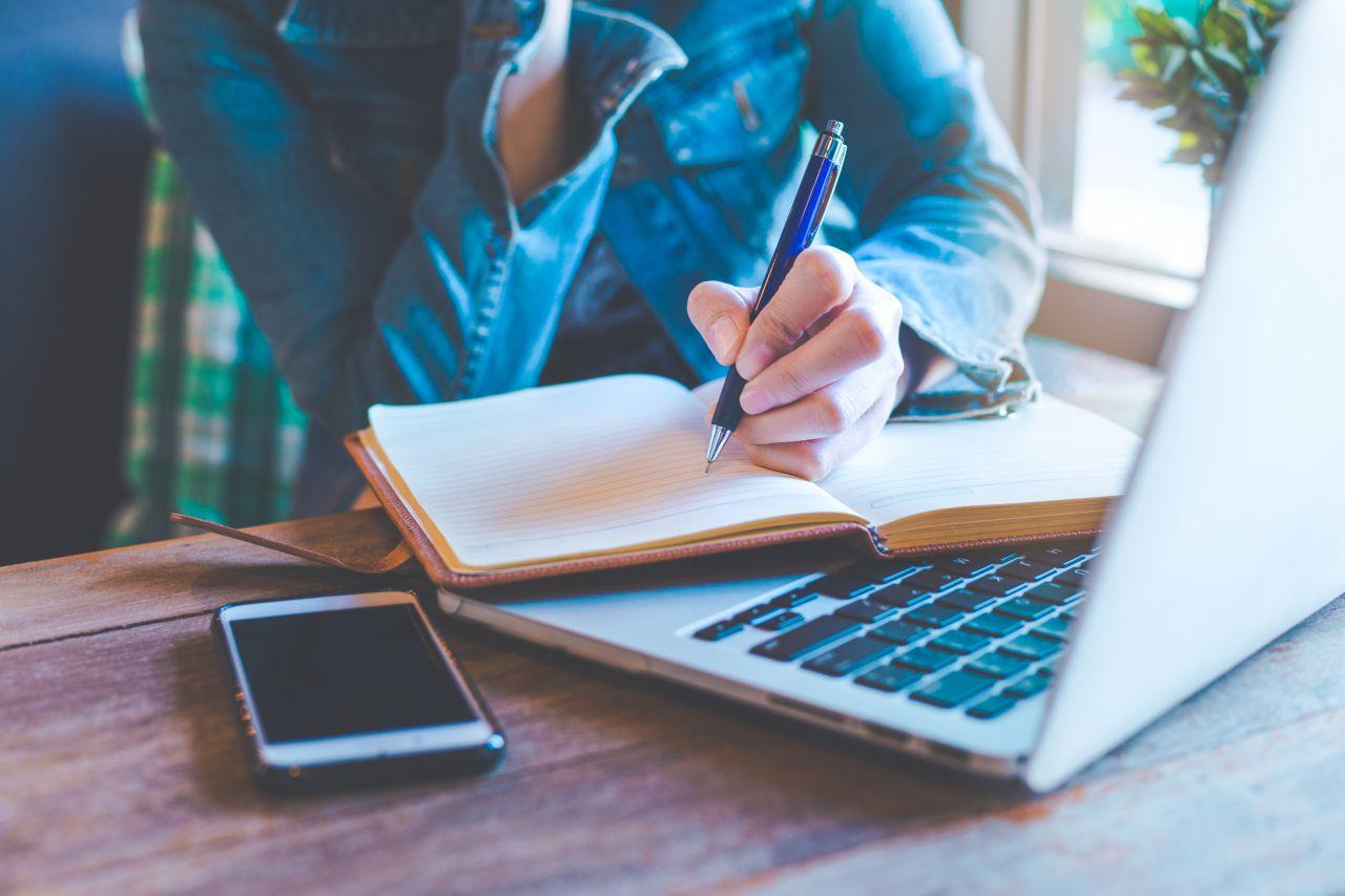 Person schreibt in ein Tagebuch