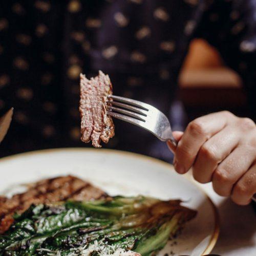 Ein junger Mann isst Fleisch
