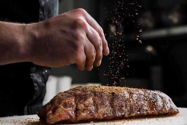 Mann würzt ein Stück Rindfleisch
