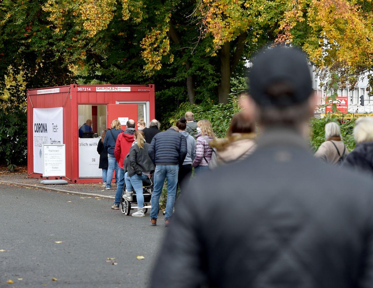 Menschen stehen in einer langen Schlange vor dem Eingang eines neuen Corona Walk-In-Testzentrums in Wuppertal, wo mittlerweile mehr als 100 Corona-Neuinfektionen pro 100.000 Einwohnern innerhalb einer Woche nachgewiesen wurden.