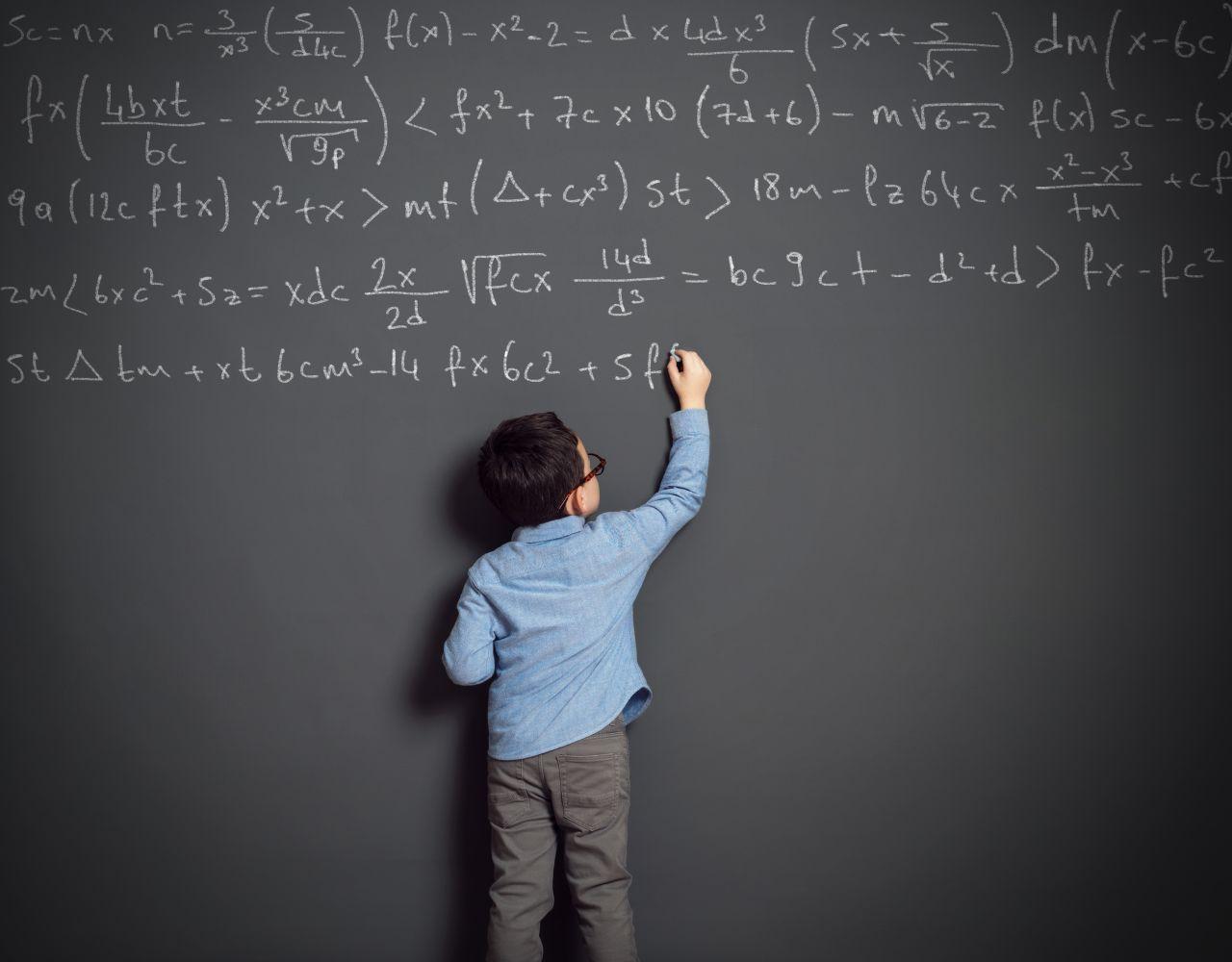 Kind schreibt Mathe-Formel an eine Tafel