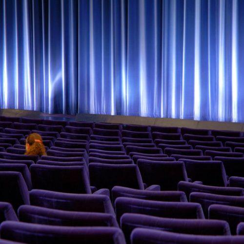 Leerer Kino-Saal mit einzelner Frau