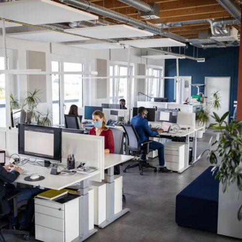 Menschen sitzen mit Maske im Büro.