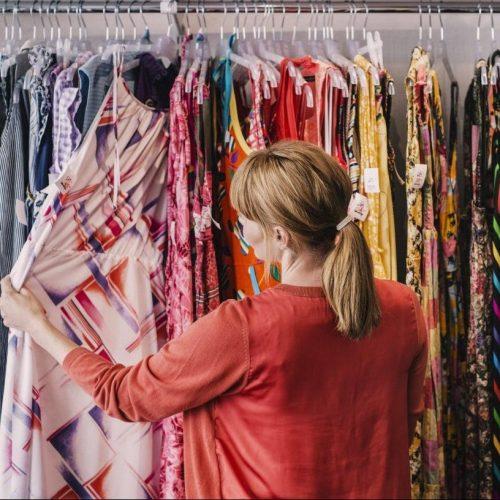 Frau kauft Second Hand Kleidung