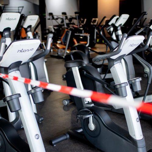 Ein rot-weißes Flatterband ist an Fahrrad-Trainern befestigt, die in einem Fitnessstudio stehen. Fitnessstudios müssen bis Januar weiter geschlossen bleiben.