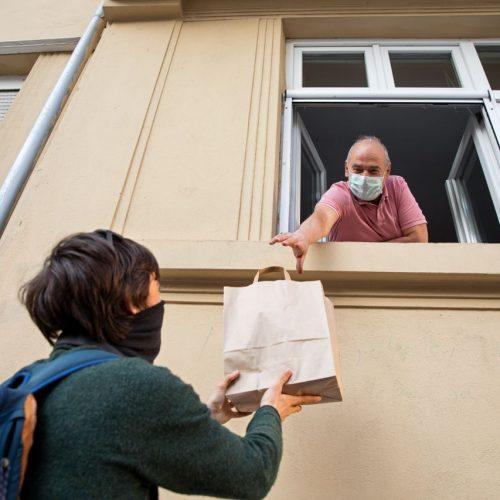 Ein Mann in Quarantäne erhält seine Einkäufe durchs Fenster