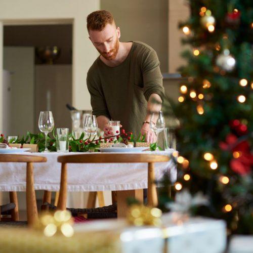Mann deckt den Weihnachts-Tisch-