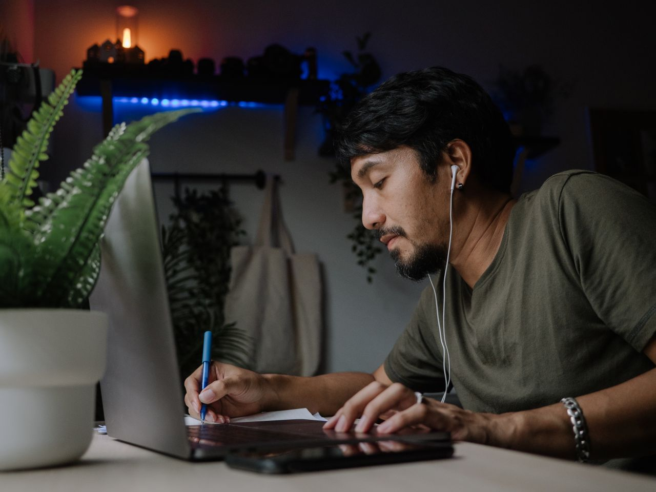Mann am Laptop macht Notizen