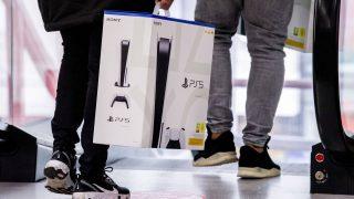 Zwei Personen gehen zur Rolltreppe, wobei einer von ihnen eine Playstation trägt