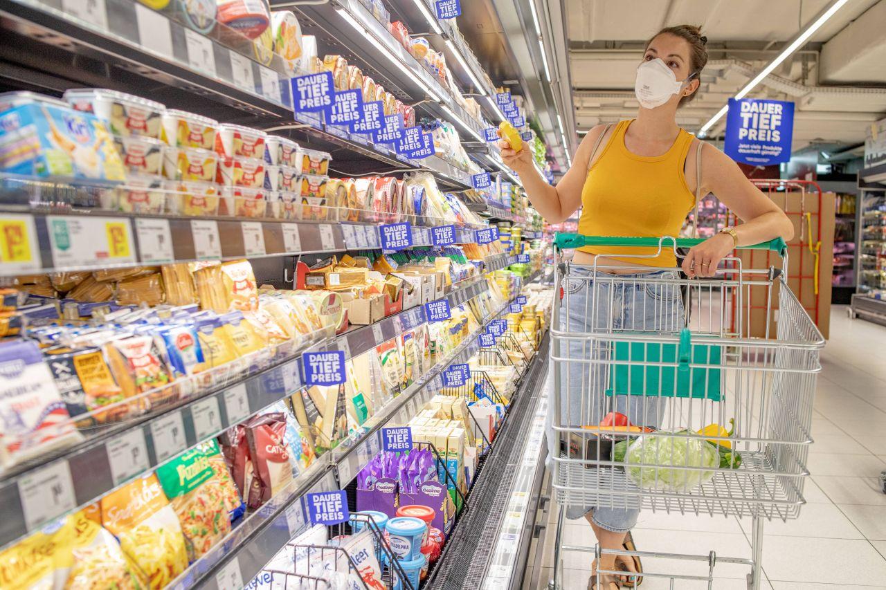 Frau vor Kühlregal in Supermarkt