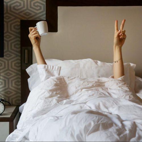 Frau streckt Hände unter Bettdecke hevor.