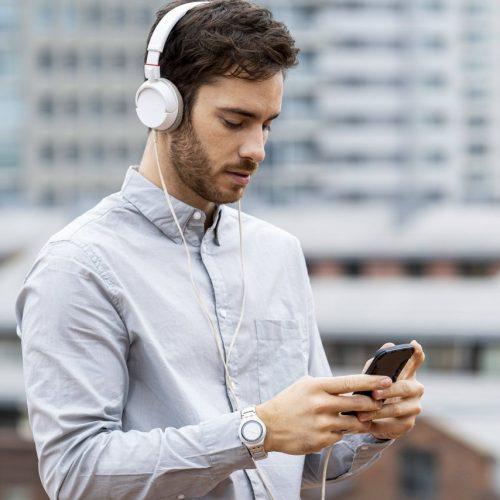 Junger Mann mit Kopfhörern und Smartphone