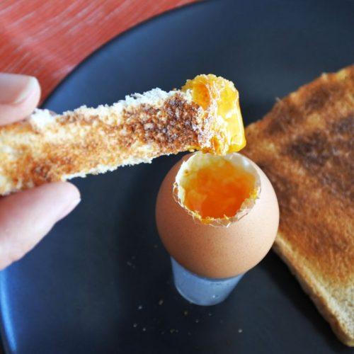 Toast wird in Frühstücksei getunkt.