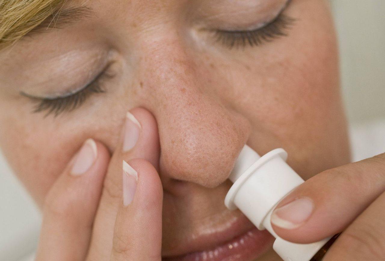 Eine Frau sprüht Nasenspray in ihre Nase.