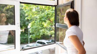 Eine Frau steht am offenen Fenster.