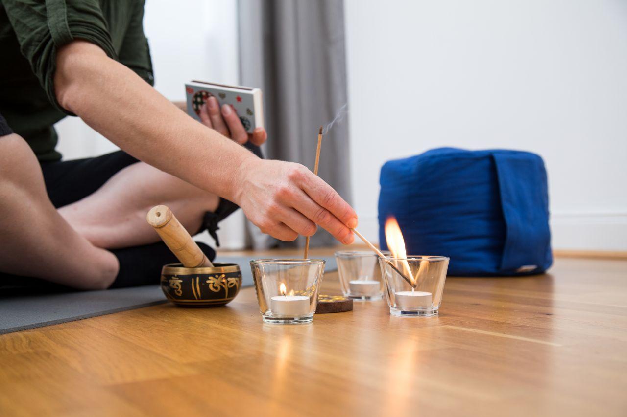 Eine Frau zündet ein Teelicht an.