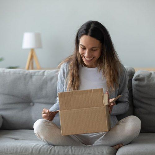 Frau auf Sofa macht Päckchen auf