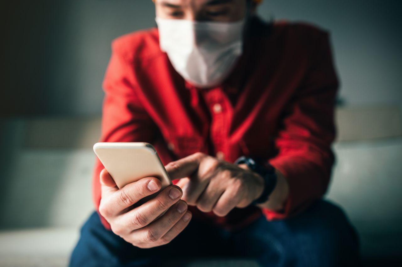 Mann mit Maske schaut auf Smartphone
