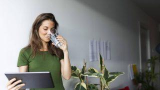 Eine junge Frau trinkt aus einem Glas Wasser.