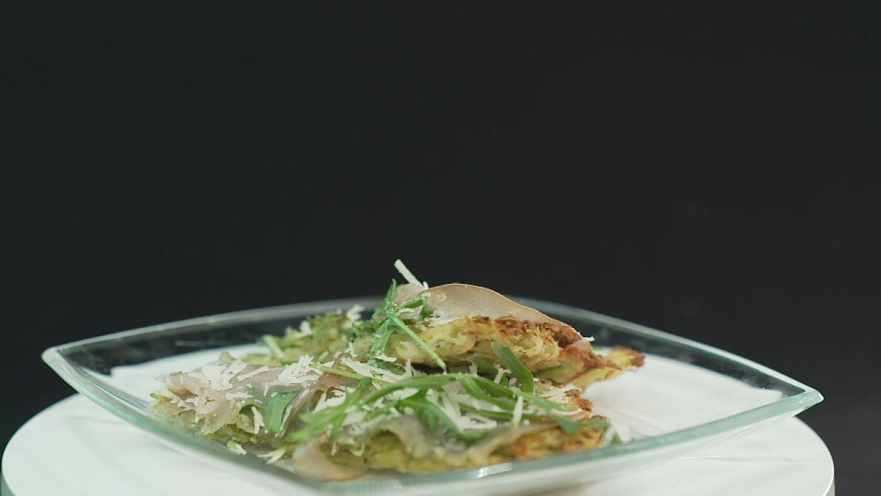 Italienische Rösti Pizzen garniert mit Rucola, Schinken und Parmesan, serviert auf einem Teller