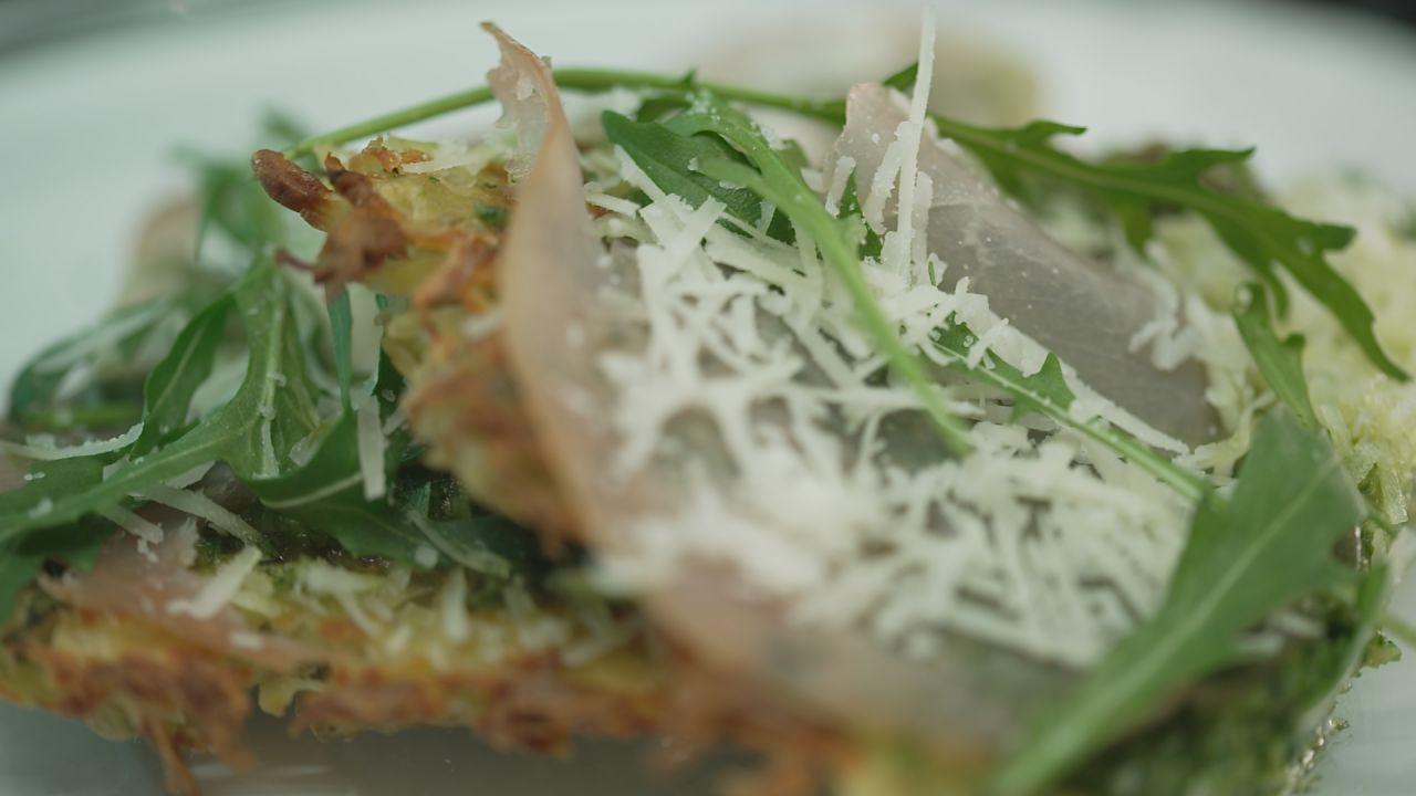 Italienische Rösti Pizzen garniert mit Rucola, Schinken und Parmesan, serviert auf einem Teller.