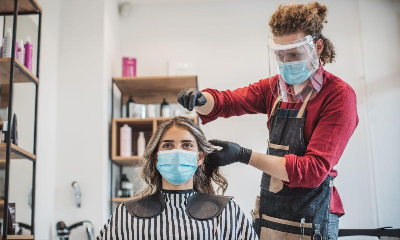 Frau sitzt während Corona beim Friseur