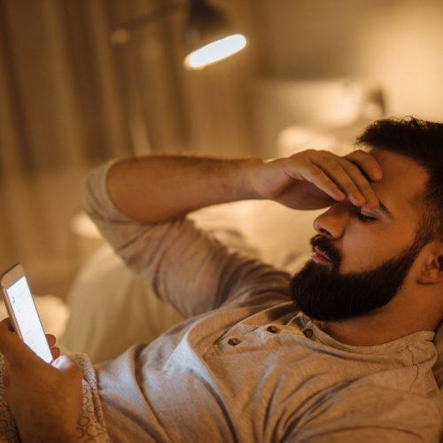 Schlechte Nachrichten noch im Bett: Ein junger Mann liest die News auf seinem Smartphone und macht sich Sorgen.