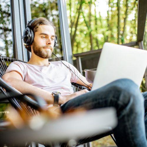 Junger Mann arbeitet mit Laptop auf Balkon