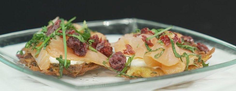 Garnierter Kartoffelpuffer mit Lachs auf einem Glasteller serviert