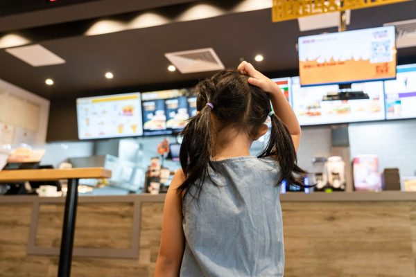 Kleines Mädchen überlegt, was sie bei McDonald's bestellen möchte.