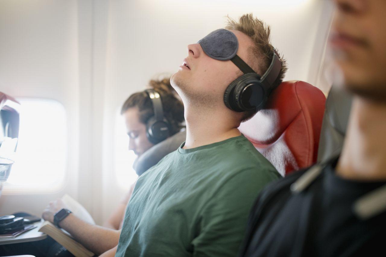 Mann schläft mit Schlafmaske in Flugzeug
