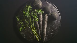 Schwarze Karotte, schwarzer Kohlrabi und Petersilie auf einer Marmorplatte