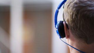 Hinterkopf eines Mannes mit On-Ear Kopfhörern