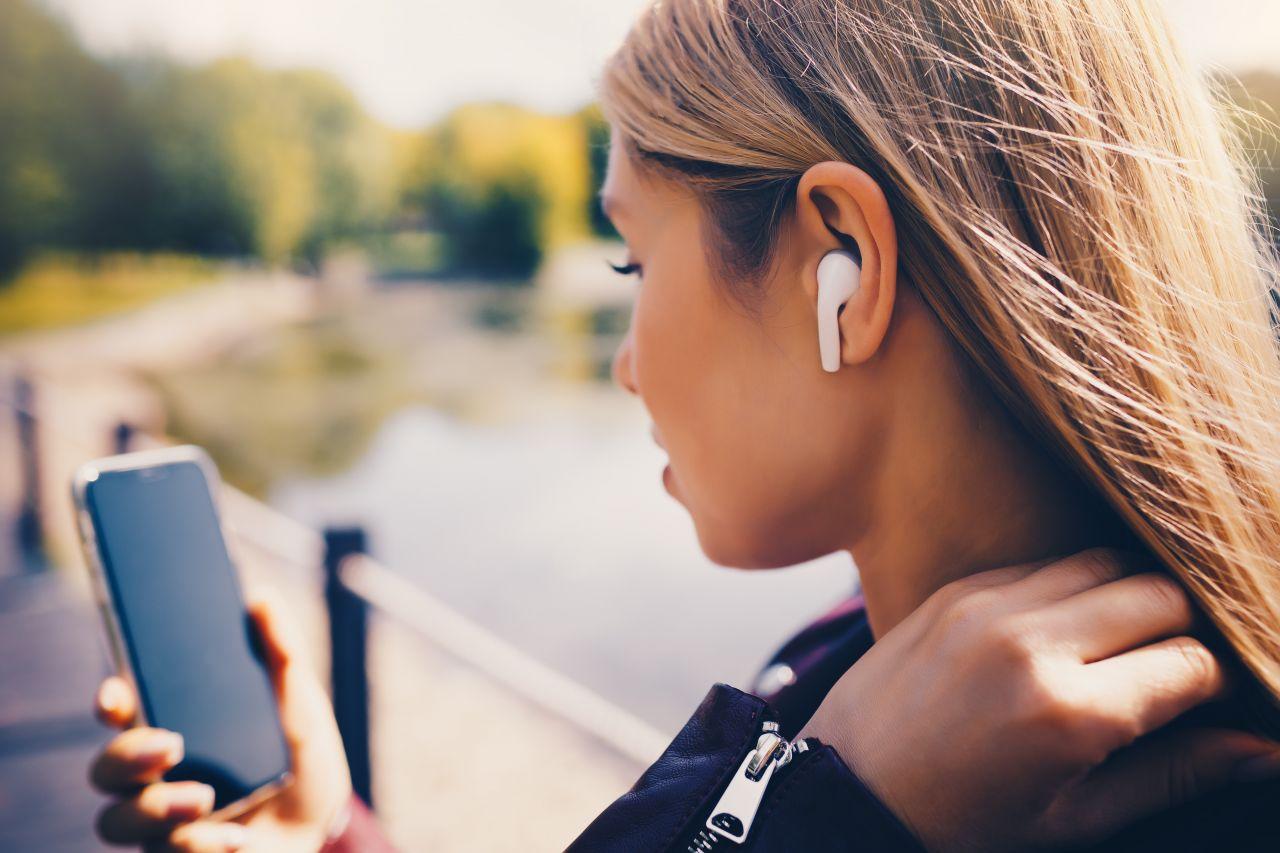 Junge Frau mit Smarphone in der Hand und In Ear Kopfhörern