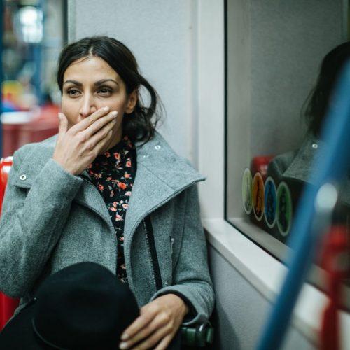 Frau gähnt in U-Bahn