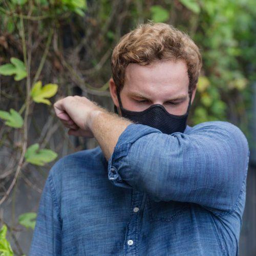 Mann mit Maske niest in Armbeuge