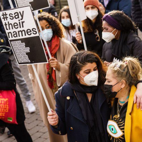 """Zwei Teilnehmerinnen stehen mit einem Plakat """"#say their names"""" auf der Kundgebung zum Gedenken an den rassistischen Anschlag 2020 in Hanau. Obwohl rassistische Diskriminierung verboten ist, gehört Rassismus in Deutschland für viele zum Alltag."""