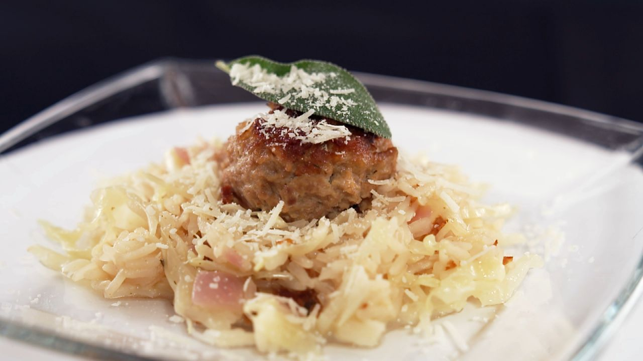 One Pot Meatball-Reis mit Kohl serviert auf einem Glasteller