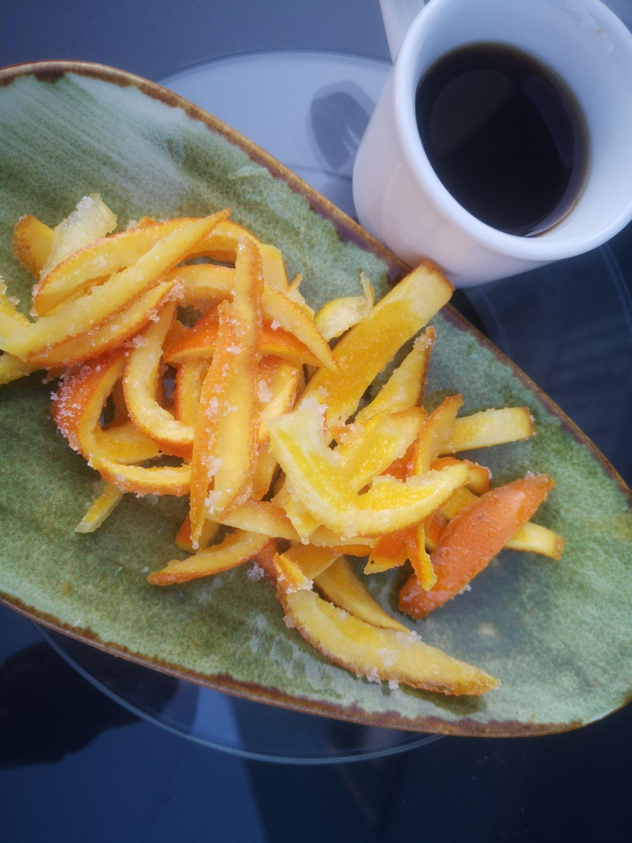 Orangenschalenfruchtgummi serviert auf einem Teller, daneben Eierschalenespresso