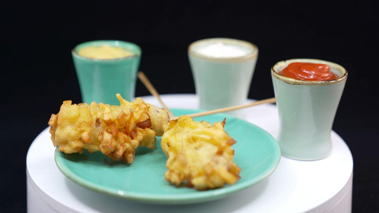 Koreanischer French Fries Hot Dog am Stiel sereviert mit Saucen in Schalen