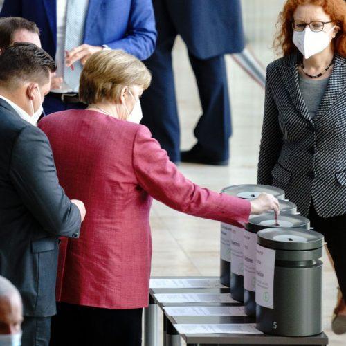 Bundeskanzlerin Angela Merkel (CDU) gibt im Bundestag ihre Stimmkarten bei der Abstimmung über die Änderung des Infektionsschutzgesetzes ab.
