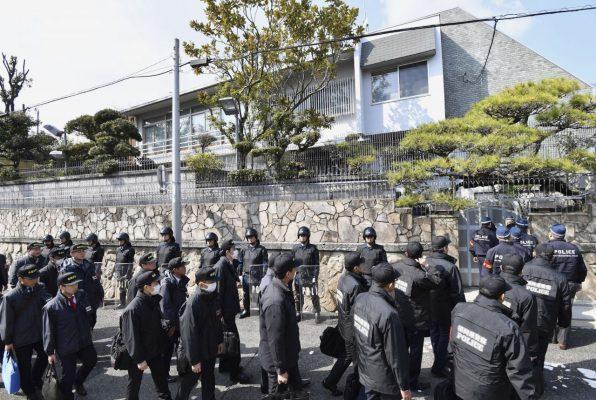 Polizeibeamte betreten das Yamaguchi-gumi-Hauptquartier, um eine Hausdurchsuchung durchzuführen.