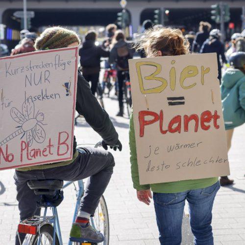 Personen mit Fahrrädern und Pappschildern auf Klimaschutz-Demonstration