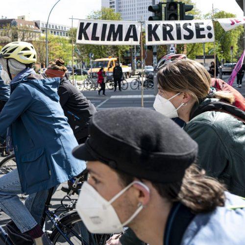 """Protestierende fahren auf einer Fridays for Future-Demo in einem Fahrradkorso vor einem Banner mit der Aufschrift """"Klima Krise""""."""