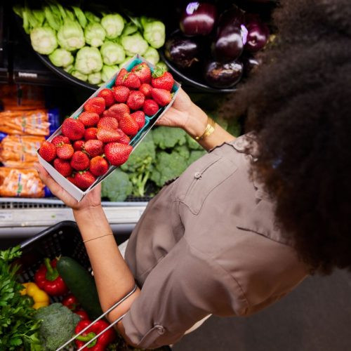 Frau kauft im Supermarkt Erdbeeren