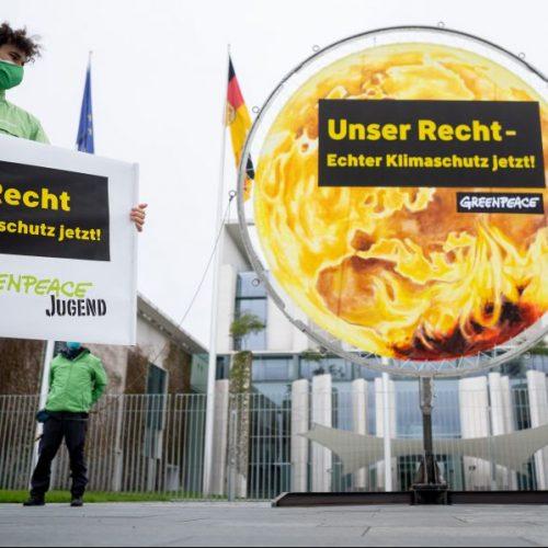 """Aktivisten der Greenpeace-Jugend protestieren mit Plakaten für ein erweitertes Klimaschutzgesetz und fordern vor dem Bundeskanzleramt """"Unser recht Klimaschutz jetzt""""."""