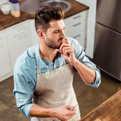 Mann schneidet Gemüse in der Küche