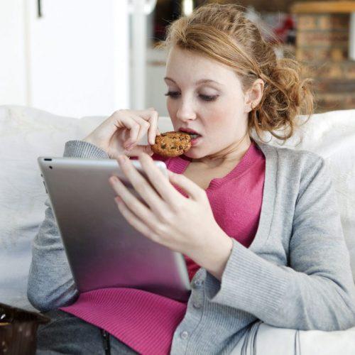 Eine Frau isst beim Online-Surfen einen Keks. Mit solchen Keksen haben Cookies im Internet nichts zu tun.